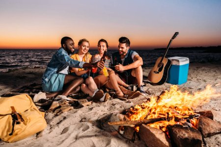 Photo for Happy multiethnic friends clinking glass bottles with drinks while spending time together on sandy beach at sunset - Royalty Free Image