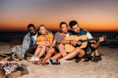 happy young multiethnic friends enjoying guitar on beach at sunset