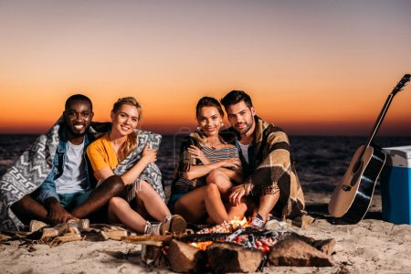 happy young people smiling at camera while sitting near bonfire on sandy beach at sunset