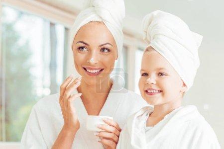 Photo pour Séduisante souriante mère et fille de peignoirs et serviettes en appliquant la crème pour le visage ensemble - image libre de droit