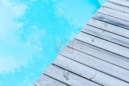 grey wooden planks and clear transparent swimming pool