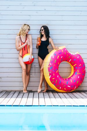 beautiful smiling young women with beach items drinking summer beverages at poolside