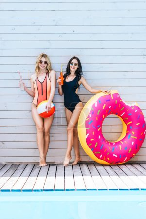 beautiful young women with beach items and summer drinks smiling at camera at poolside