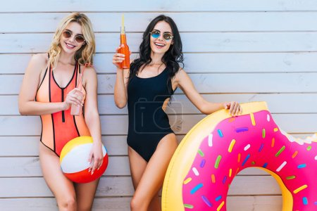 attractive girls with beach items and summer drinks smiling at camera at poolside
