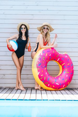 beautiful girls holding bottles with refreshing beverages and beach items, smiling at camera near swimming pool