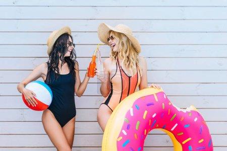 Photo pour Belles filles souriantes tinter les bouteilles de boissons rafraîchissantes et la tenue des Articles de plage au bord de la piscine - image libre de droit