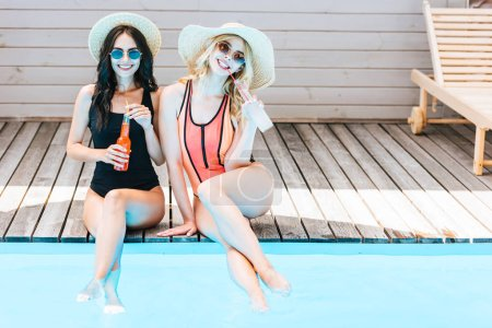 beautiful young women in swimwear drinking summer beverages and smiling at camera near pool