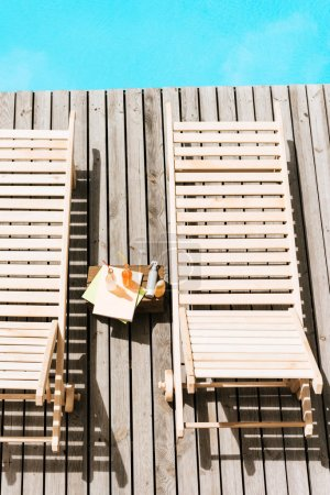 high angle view of empty chaise lounges and bottles with summer drinks near swimming pool