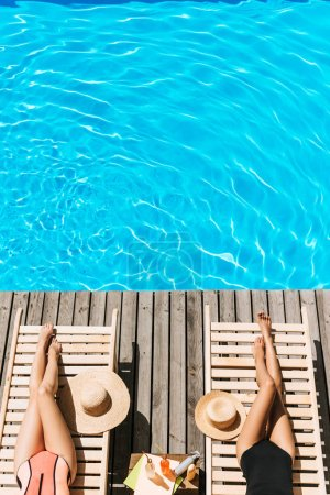 cropped shot of young women in swimwear resting on chaise lounges near swimming pool