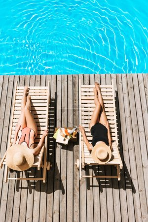 Photo for High angle view of young girlfriends lying on chaise lounges near swimming pool - Royalty Free Image
