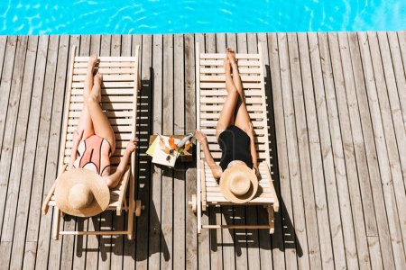 high angle view of young women resting on chaise lounges near swimming pool