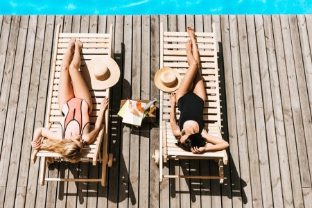top view of young women tanning on chaise lounges near swimming pool