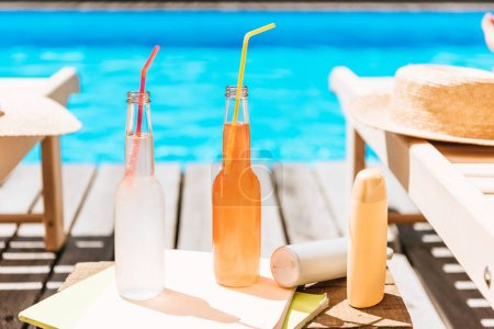 close-up view of bottles with summer drinks, sunscreen and chaise lounges at swimming pool
