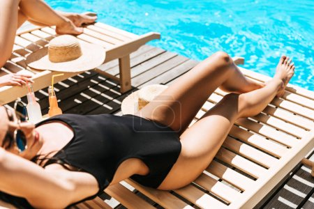 cropped shot of beautiful young women in swimwear lying on chaise lounges near swimming pool