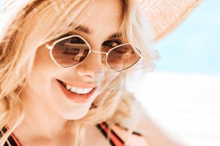 Photo pour Portrait de belle jeune femme blonde en lunettes de soleil et chapeau en osier souriant à la caméra au bord de la piscine - image libre de droit