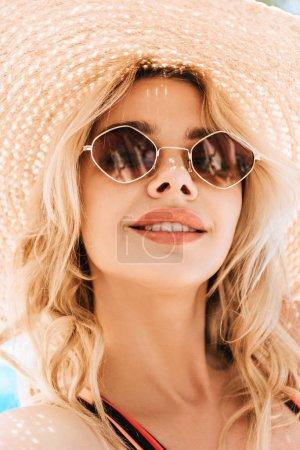 Portrait de souriante belle jeune femme blonde à lunettes de soleil et chapeau en osier