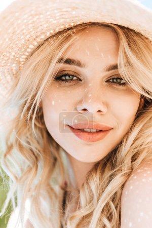Photo pour Portrait de la belle jeune femme blonde au chapeau de paille souriant à la caméra - image libre de droit
