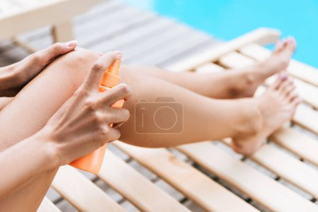close-up partial view of girl applying sunscreen at poolside