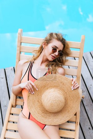 Photo for High angle view of beautiful woman in swimsuit and sunglasses holding straw hat and resting on chaise lounge near pool - Royalty Free Image