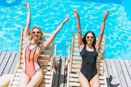 Photo pour Vue grand angle de jeunes femmes souriantes reposant sur des chaises longues près de la piscine - image libre de droit