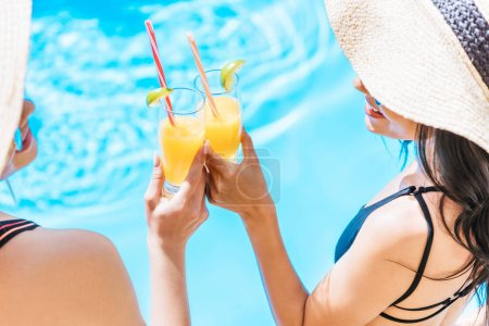 cropped shot of young women in swimwear and hats holding glasses with refreshing beverages at pool