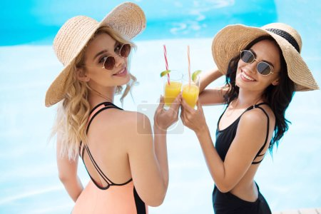 smiling young women in swimsuits and sunglasses holding refreshing beverages at swimming pool