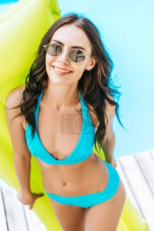 Photo for High angle view of beautiful brunette girl in bikini and sunglasses holding inflatable mattress and smiling at camera at poolside - Royalty Free Image