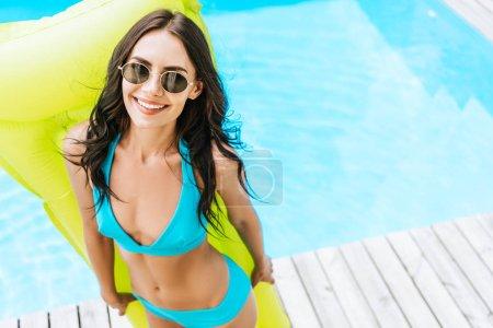 Foto de Vista de ángulo alto de hermosa mujer joven en bikini y gafas de sol sosteniendo el colchón inflable y sonriendo a cámara junto a piscina - Imagen libre de derechos