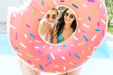 happy young women in sunglasses and swimwear holding swimming doughnut and smiling at camera near pool