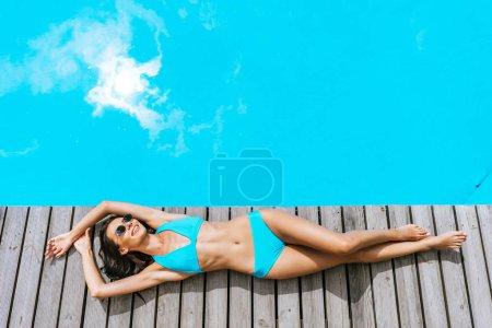 top view of beautiful smiling brunette woman in bikini and sunglasses resting near pool