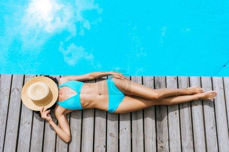 top view of girl in bikini and straw hat on face lying near swimming pool