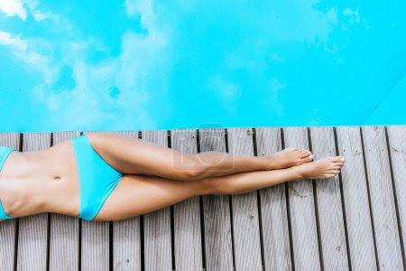 cropped shot of young woman in bikini lying near swimming pool