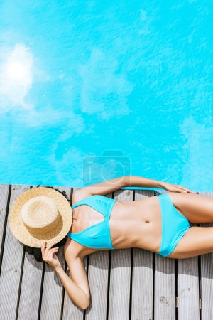 top view of young woman in bikini and straw hat on face lying near swimming pool