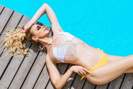 Foto de Vista de ángulo alto de hermosa mujer rubia en bikini y gafas de sol de mentira junto a la piscina - Imagen libre de derechos