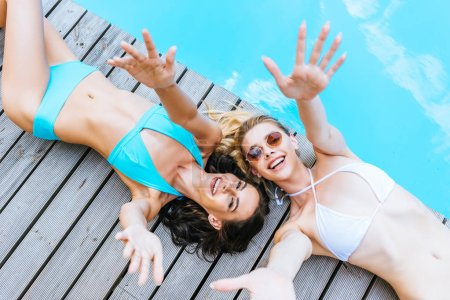 top view of happy young women in sunglasses and swimwear reaching arms and smiling at camera near pool