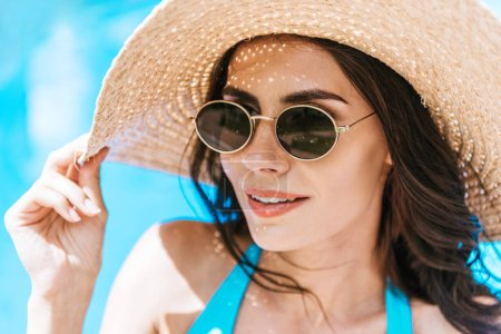 Photo for Beautiful brunette woman in sunglasses and straw hat smiling at poolside - Royalty Free Image