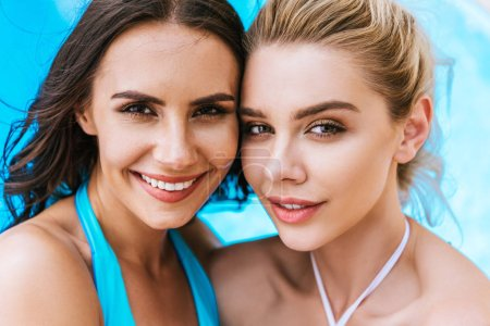 Photo for Beautiful young women in swimwear smiling at camera near swimming pool - Royalty Free Image