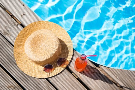 top view of wicker hat, sunglasses and bottle with summer drink near swimming pool