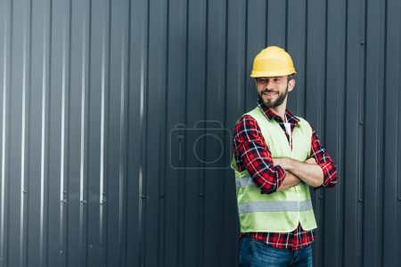 male worker in safety vest and helmet standing with crossed arms near wall