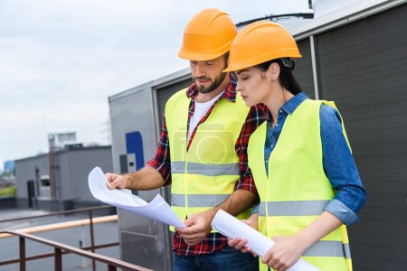 professional architects in helmets working with blueprints on roof