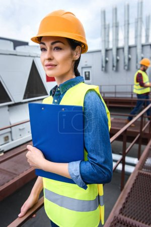 female architect in helmet holding clipboard on roof, male colleague behind