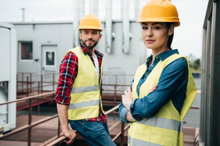 Photo for Professional architects in safety vests and helmets posing on roof - Royalty Free Image