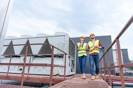 Photo pour Ingénieurs en casques avec blueprint, café pour aller et niveau marcher sur le toit - image libre de droit