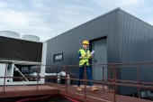 professional female engineer in safety vest and hardhat with blueprint on coffee break on roof
