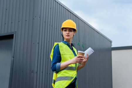 beautiful female engineer in safety vest with blueprint and coffee to go