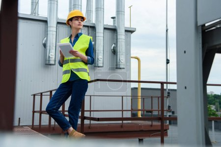 professional female engineer in safety vest and helmet using tablet on industrial construction