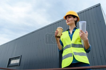 beautiful female engineer in safety vest and helmet with blueprint and disposable cup on coffee