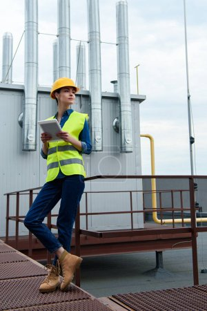 female architect in safety vest and hardhat using digital tablet on industrial construction