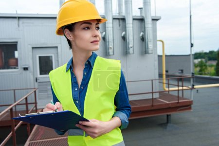 beautiful female engineer writing in clipboard on industrial construction