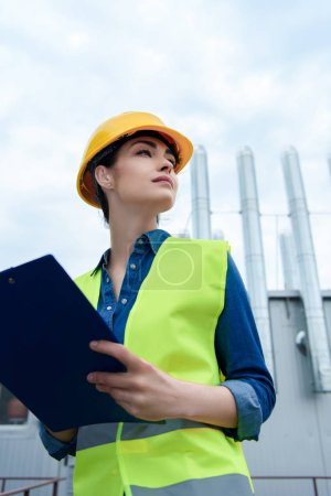 Photo for Bottom view of beautiful female architect in safety vest and hardhat writing in clipboard - Royalty Free Image